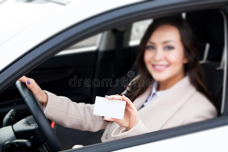 conducteur de femme tenant une carte de visite professionnelle vierge blanche de visite images stock