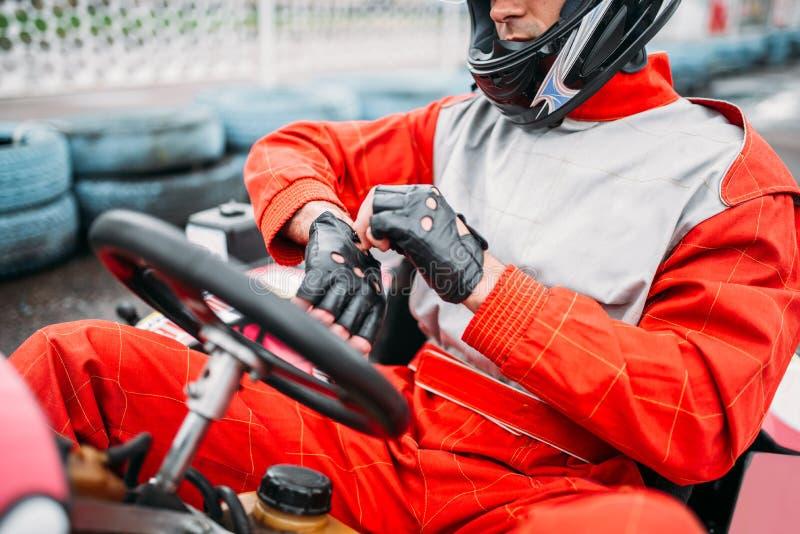 Conducteur de kart dans le casque sur la voie karting de vitesse photos stock