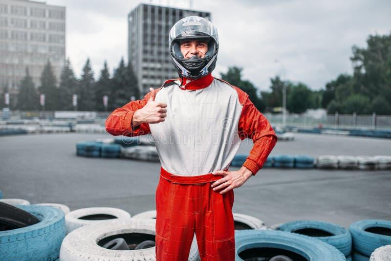 Conducteur de kart dans le casque, voie karting sur le fond image stock