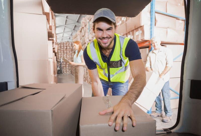 Conducteur de la livraison chargeant son fourgon avec des boîtes photos stock