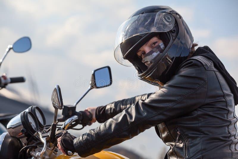 Conducteur de moto dans l'équipement noir tenant le volant et regardant l'appareil-photo, femme caucasienne photographie stock libre de droits