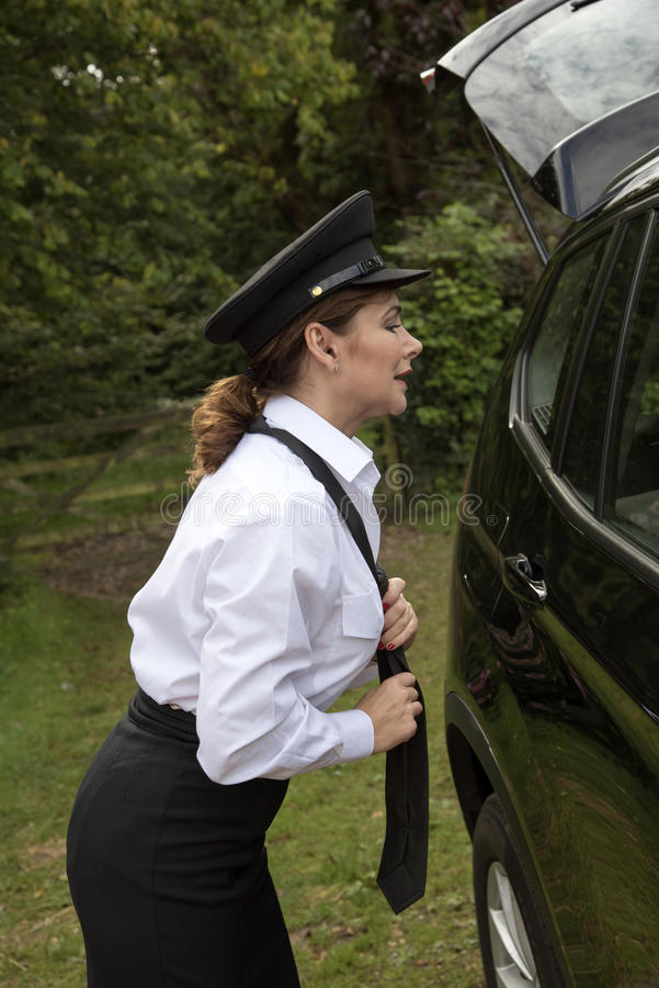 Conducteur de voiture femelle professionnel ajustant son lien image libre de droits