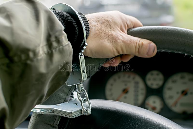 Conducteur de voiture menotté au volant, arrestation, interdiction de conduire photographie stock libre de droits