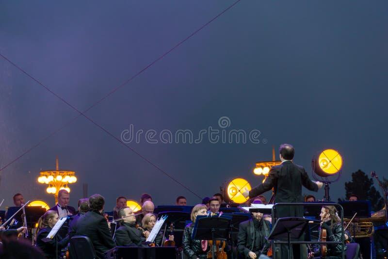 Conducteur dirigeant l'orchestre symphonique avec des interpr?tes sur le fond photos stock
