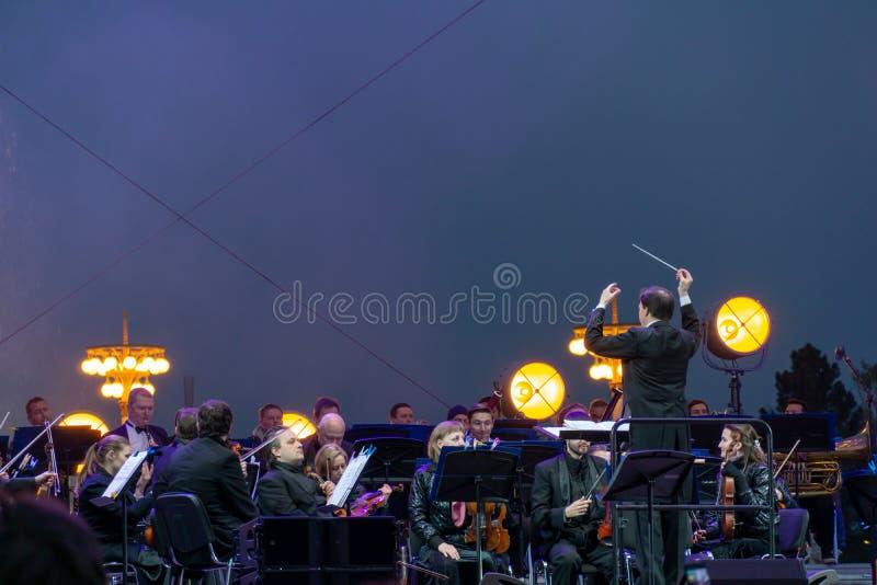 Conducteur dirigeant l'orchestre symphonique avec des interpr?tes sur le fond photo stock