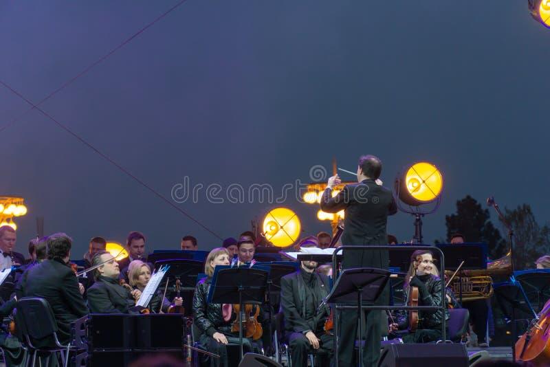 Conducteur dirigeant l'orchestre symphonique avec des interpr?tes sur le fond images libres de droits