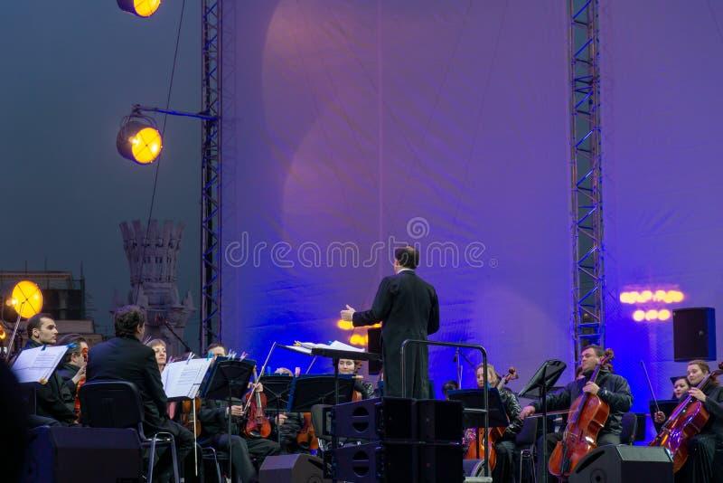 Conducteur dirigeant l'orchestre symphonique avec des interpr?tes sur le fond images stock