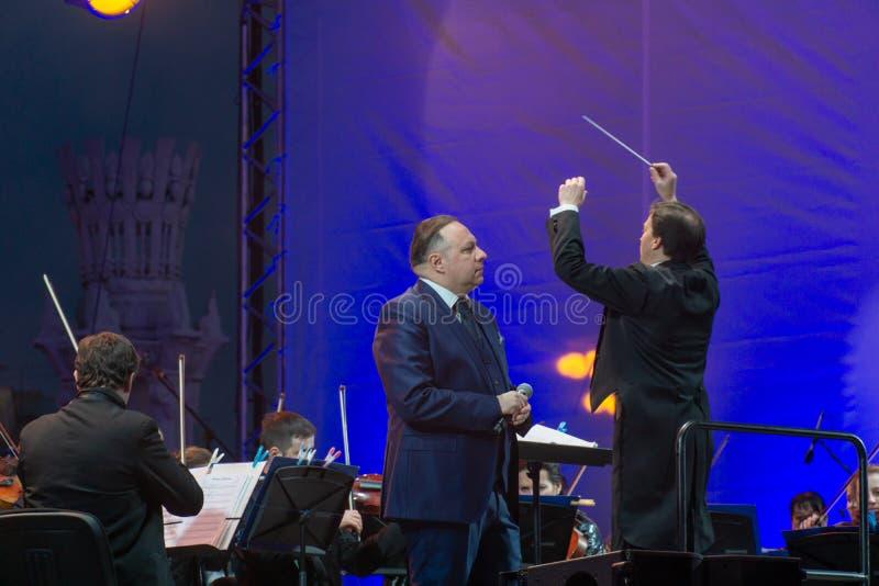 Conducteur dirigeant l'orchestre symphonique avec des interpr?tes sur le fond image stock