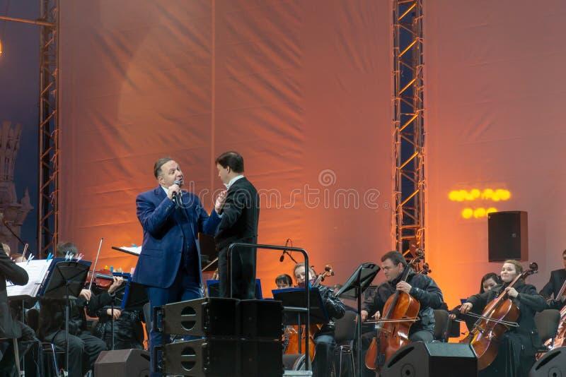 Conducteur dirigeant l'orchestre symphonique avec des interpr?tes sur le fond photographie stock
