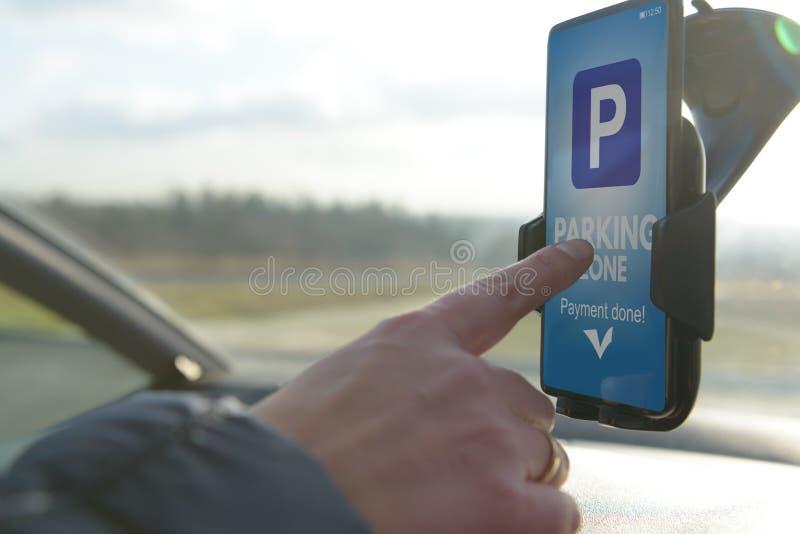 Conducteur employant l'appli de smartphone pour payer se garer image libre de droits