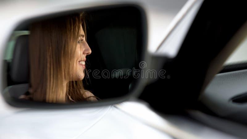 Conducteur femelle heureux se reposant dans la voiture et souriant à l'ami, rétroviseur photos stock