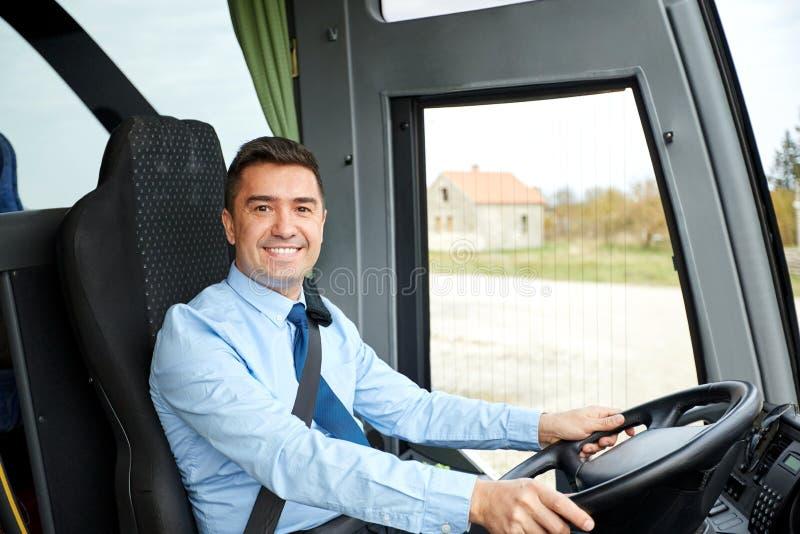 Conducteur heureux conduisant l'autobus interurbain photos stock