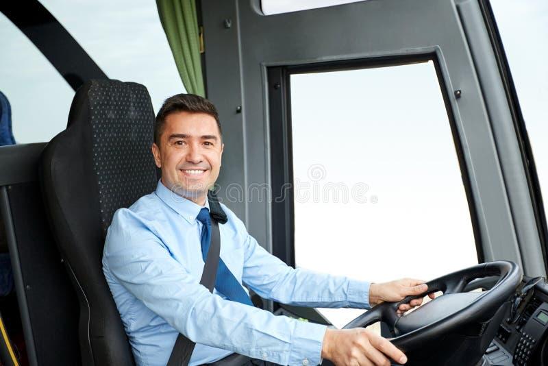 Conducteur heureux conduisant l'autobus interurbain images stock