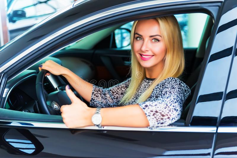 Conducteur heureux de femme montrant des pouces dans sa voiture photos stock