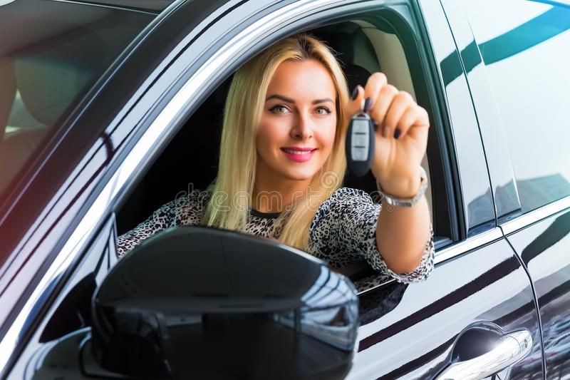 Conducteur heureux de femme tenant des clés automatiques dans sa voiture image stock