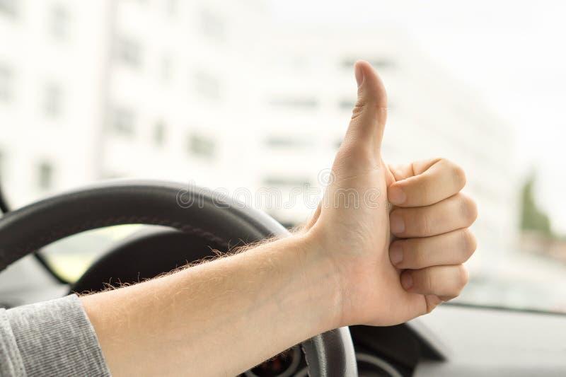 Conducteur heureux montrant des pouces dans la voiture images libres de droits
