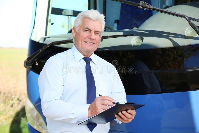 Conducteur professionnel avec le presse-papiers près de l'autobus photo stock