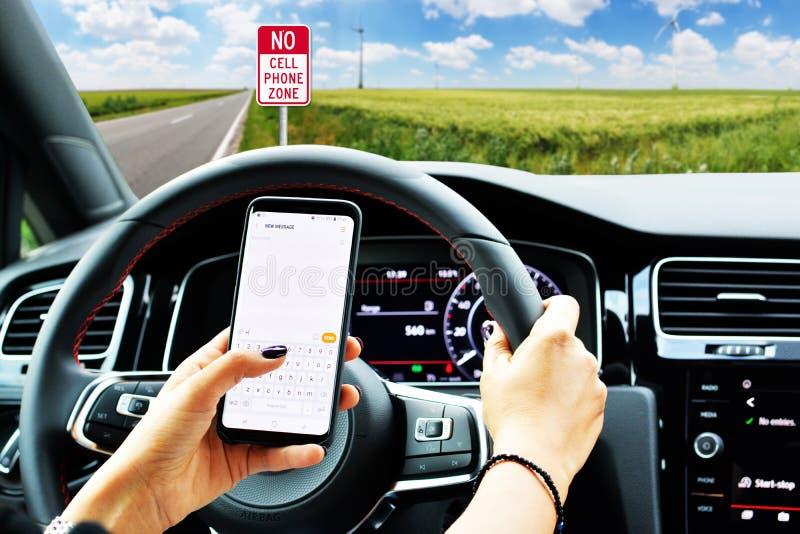 Conducteur soigneux dans la voiture cessée du côté droit de la route pour écrire un message au smartphone ; aucun avertissement d image libre de droits