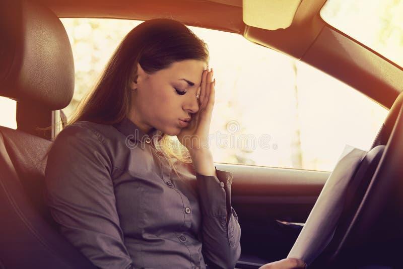 Conducteur soumis à une contrainte de femme avec des papiers se reposant à l'intérieur de sa voiture image libre de droits