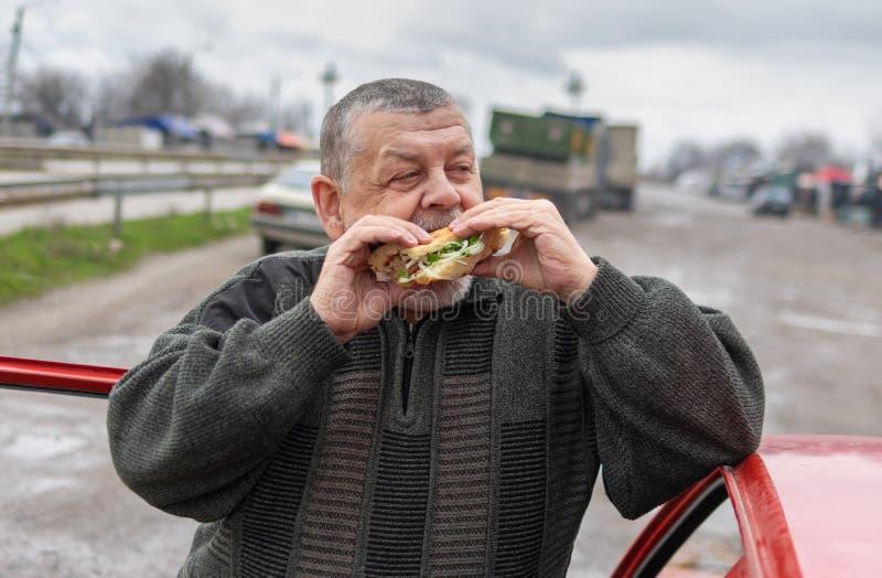 Conducteur supérieur avalant le chiche-kebab de lyulya dans le lavash près de sa voiture image libre de droits