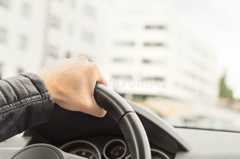 Conducteur tenant le volant avec une main photo stock
