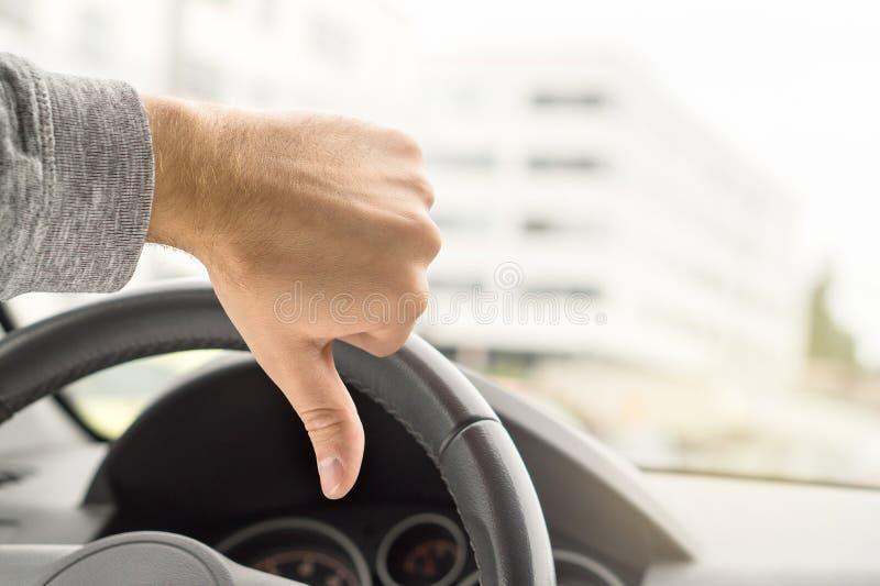 Conducteur triste montrant des pouces dans la voiture Homme mécontent photo libre de droits