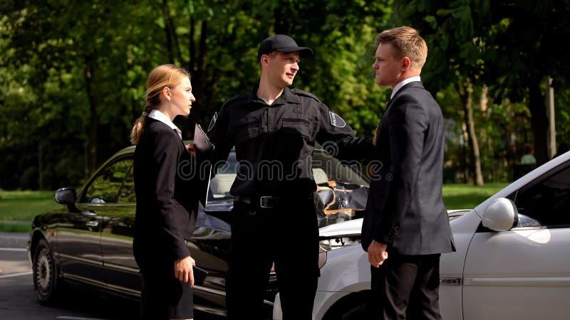Conducteurs en colère se regardant, policier réglant la collision de la circulation, accident image libre de droits
