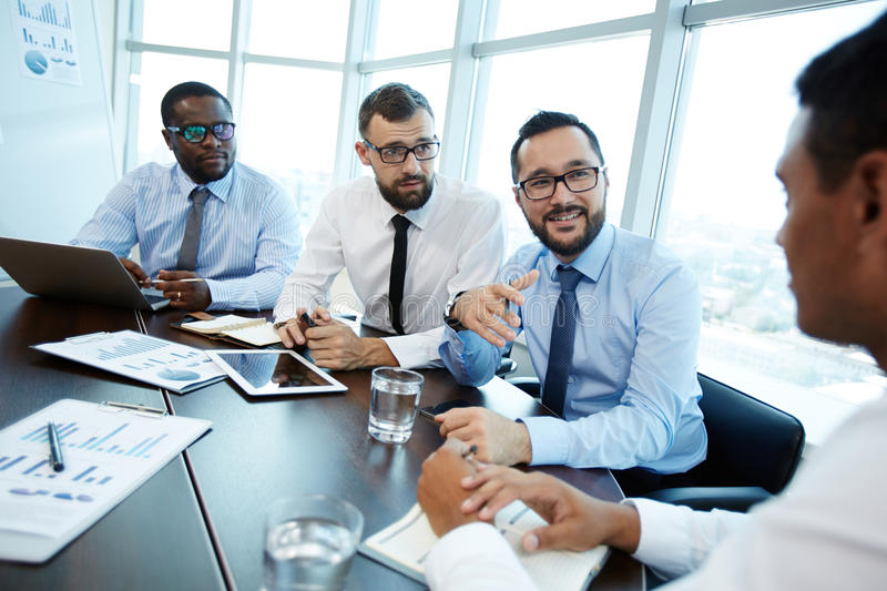 Conducting Negotiations with Business Partner. Three bearded employees in eyeglasses conducting negotiations with their business partner while sitting in modern royalty free stock photography