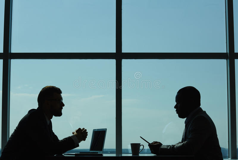 Conducting Negotiations in Modern Boardroom. Profile view of two confident business partners conducting negotiations while sitting in modern dim boardroom royalty free stock image