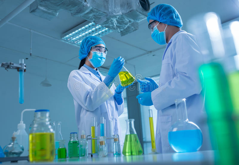 Conducting research. Asian team of chemists conducting research in the laboratory royalty free stock images