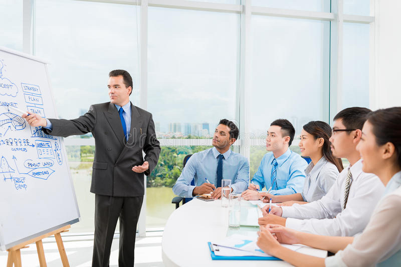 Conducting training. Caucasian businessman conducting training for his multi-ethnic employees royalty free stock image