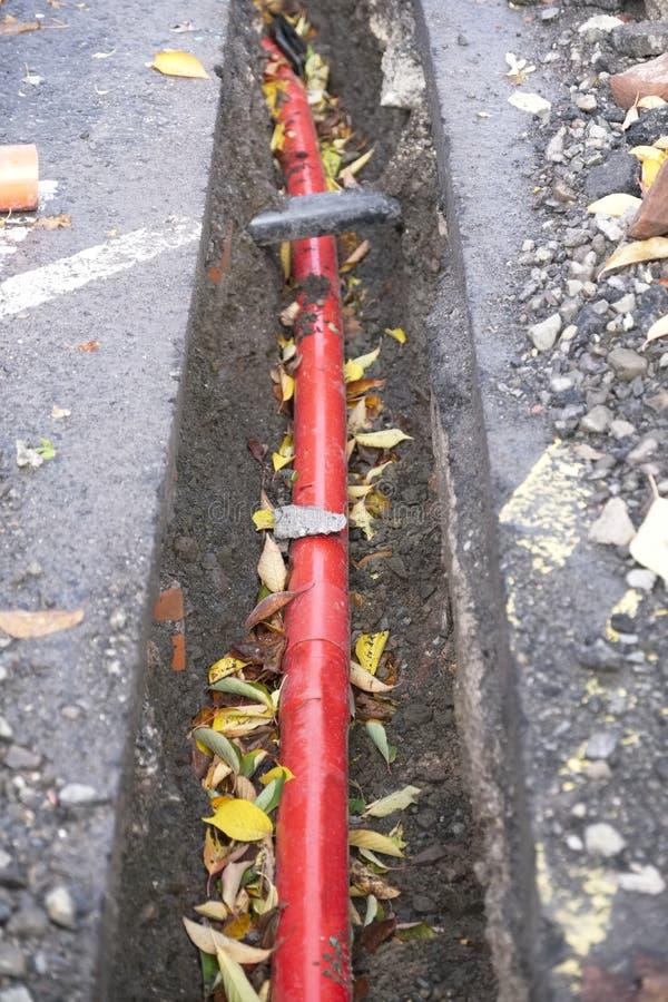 Conducto de cable rojo eléctrico subterráneo en foso en el solar de la construcción imagen de archivo