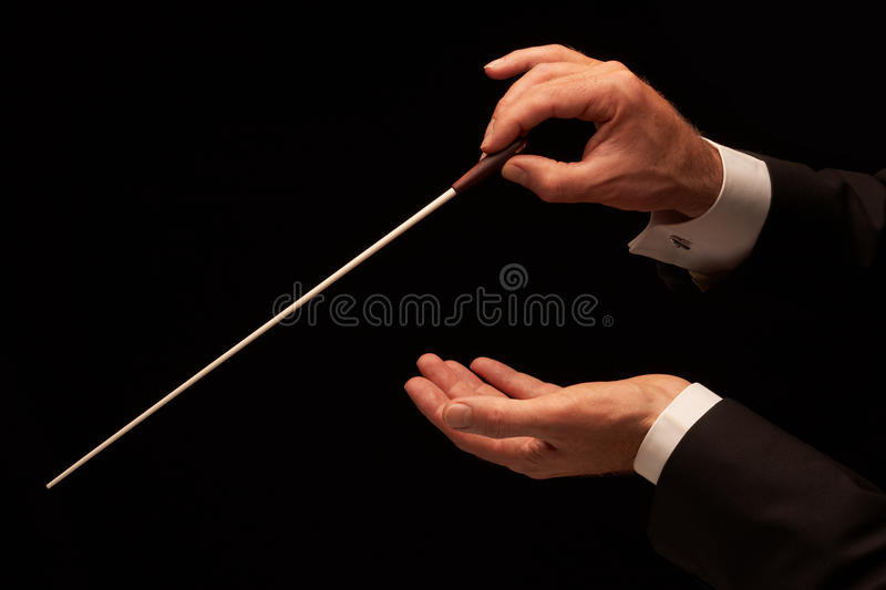 Conductor conducting an orchestra. Isolated on black background stock image