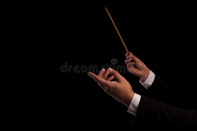 Conductor conducting an orchestra. Conductor`s hands conducting an orchestra on black studio background stock photography