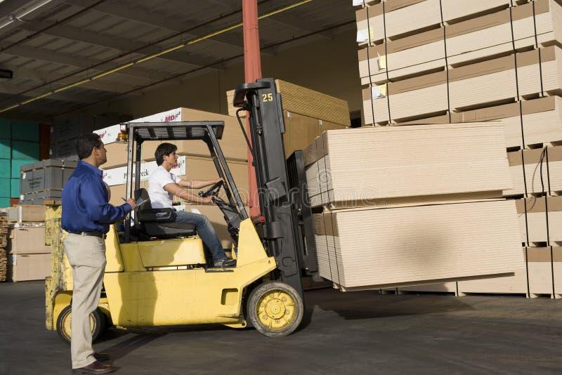Conductor de camión In Timber Factory del encargado del almacén y de la carretilla elevadora fotos de archivo libres de regalías