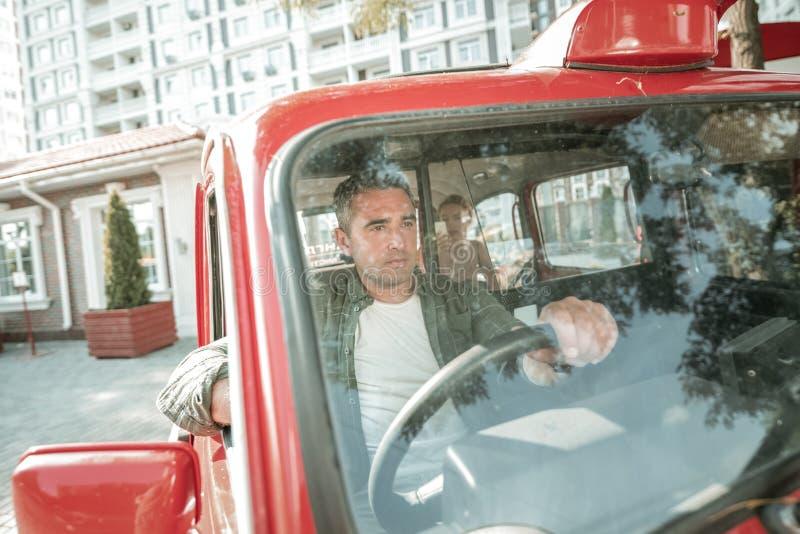 Conductor de coche serio en su manera al centro de la ciudad foto de archivo libre de regalías