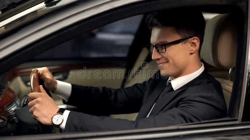 Conductor de la clase de negocios que se sienta en el coche, satisfecho con nuevo trabajo, auto costoso imagen de archivo