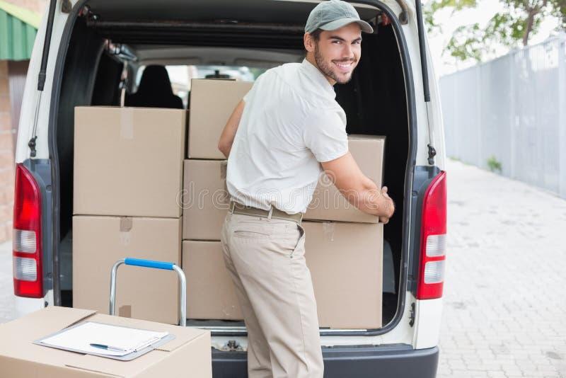 Conductor de la entrega que carga su furgoneta con las cajas foto de archivo