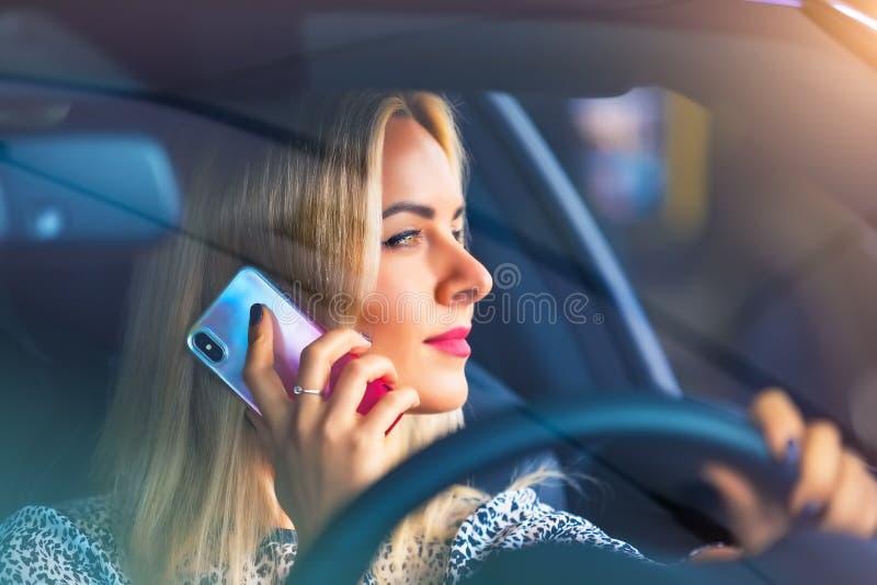 Conductor de la mujer joven que habla por el teléfono en el coche foto de archivo libre de regalías