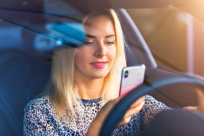 Conductor de la mujer joven que usa un smartphone en el coche fotos de archivo