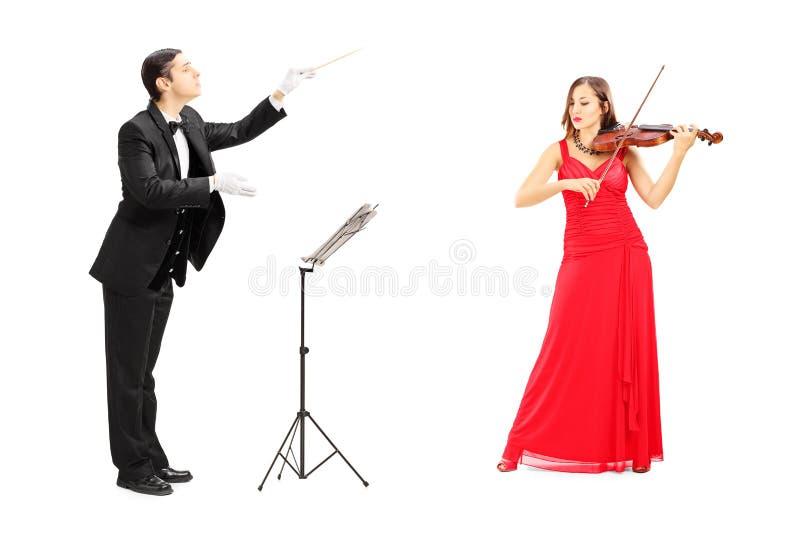 Conductor de orquesta de sexo masculino que dirige un violín que juega femenino imagen de archivo