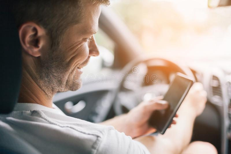 Conductor descuidado que usa un teléfono móvil mientras que conduce imagen de archivo libre de regalías