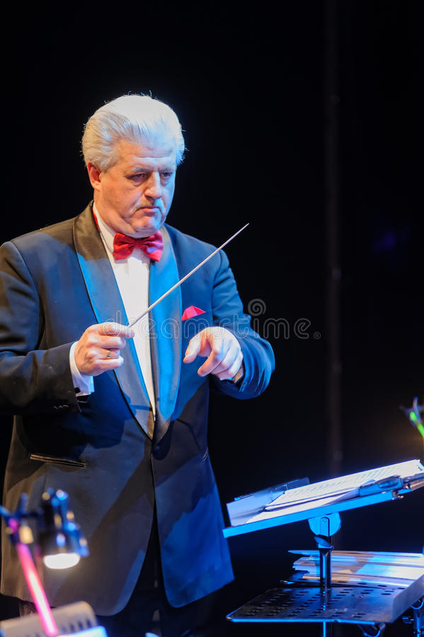 Conductor directing orchestra. Tyumen, Russia - April 16, 2014: Competition of young performers the Song knows no limit in dramatic theater. Conductor directing royalty free stock photos