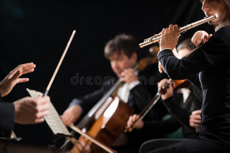 Conductor directing symphony orchestra. In concert with flutist on foreground stock photo