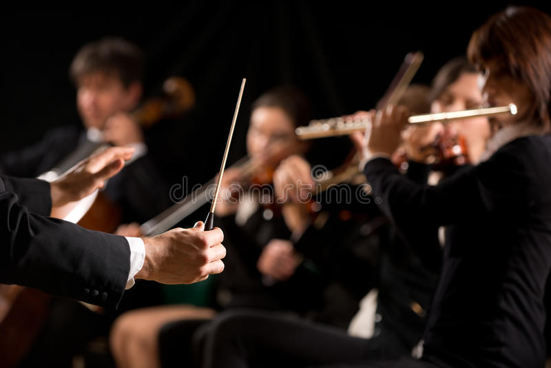Conductor directing symphony orchestra. With performers on background royalty free stock photos