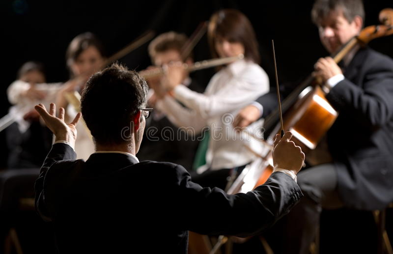 Conductor directing symphony orchestra. With performers on background royalty free stock photography