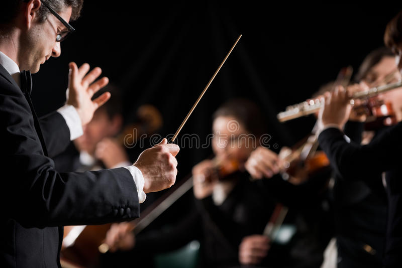 Conductor directing symphony orchestra. With performers on background stock photos
