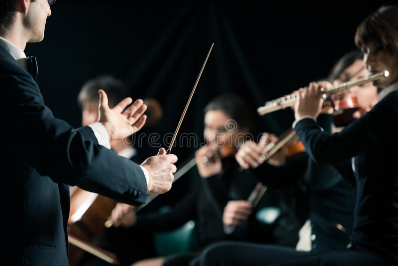 Conductor directing symphony orchestra. With performers on background stock photo