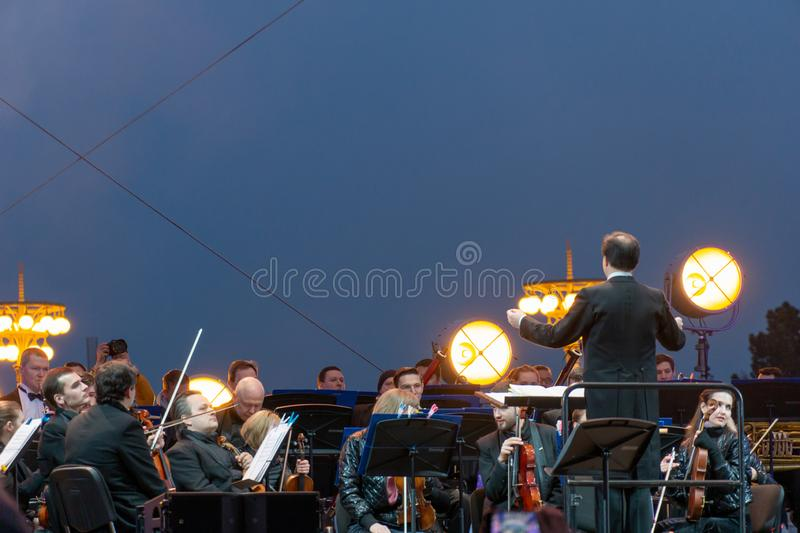 Conductor directing symphony orchestra with performers on background. Russia, Moscow, April 30, 2019: Conductor directing symphony orchestra with performers on stock photos