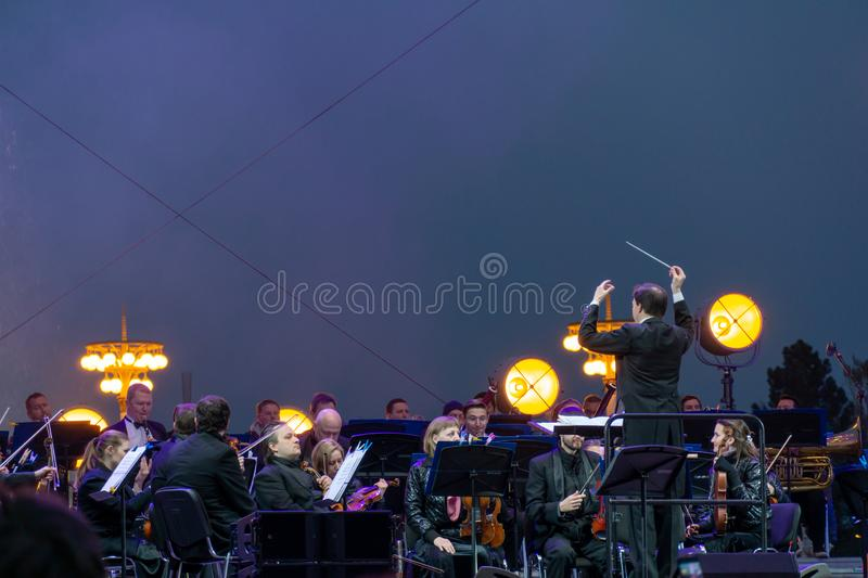 Conductor directing symphony orchestra with performers on background. Russia, Moscow, April 30, 2019: Conductor directing symphony orchestra with performers on stock photo